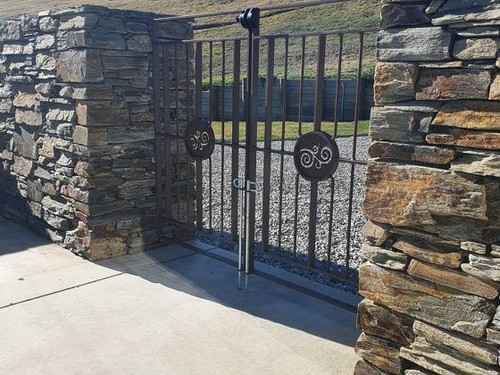 Iron and stone gateway with automatic gate by Otago Engineering