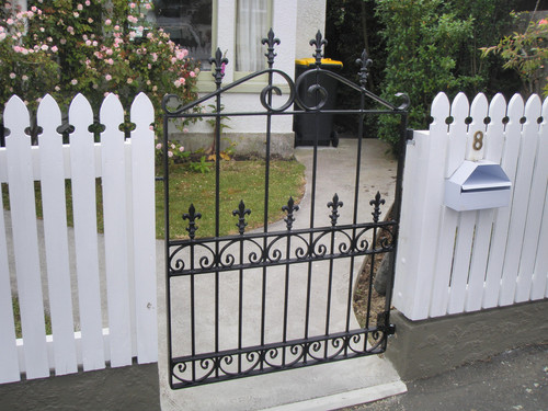 Decorative wrought iron gate with white picket fence