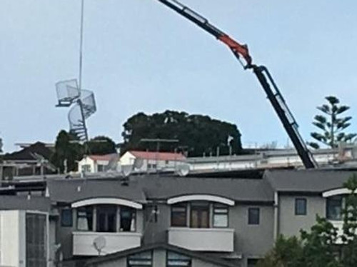 A crane lowering the Spiral Staircase into position, manufactured by Otago Engineering