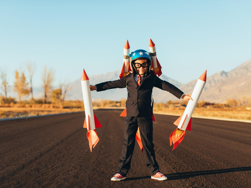 Boy holding rockets shows the choice between custom websites and template websites
