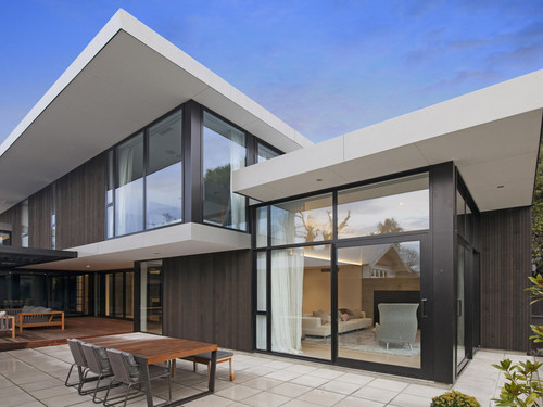 This Christchurch home features flat roofs and swooping soffits.
