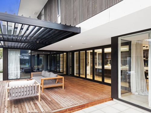 The exterior features floor to ceiling windows and doors
