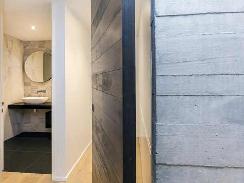 The home uses a mix of materials including concrete, marble, steel framing and  grooved cedar weatherboard