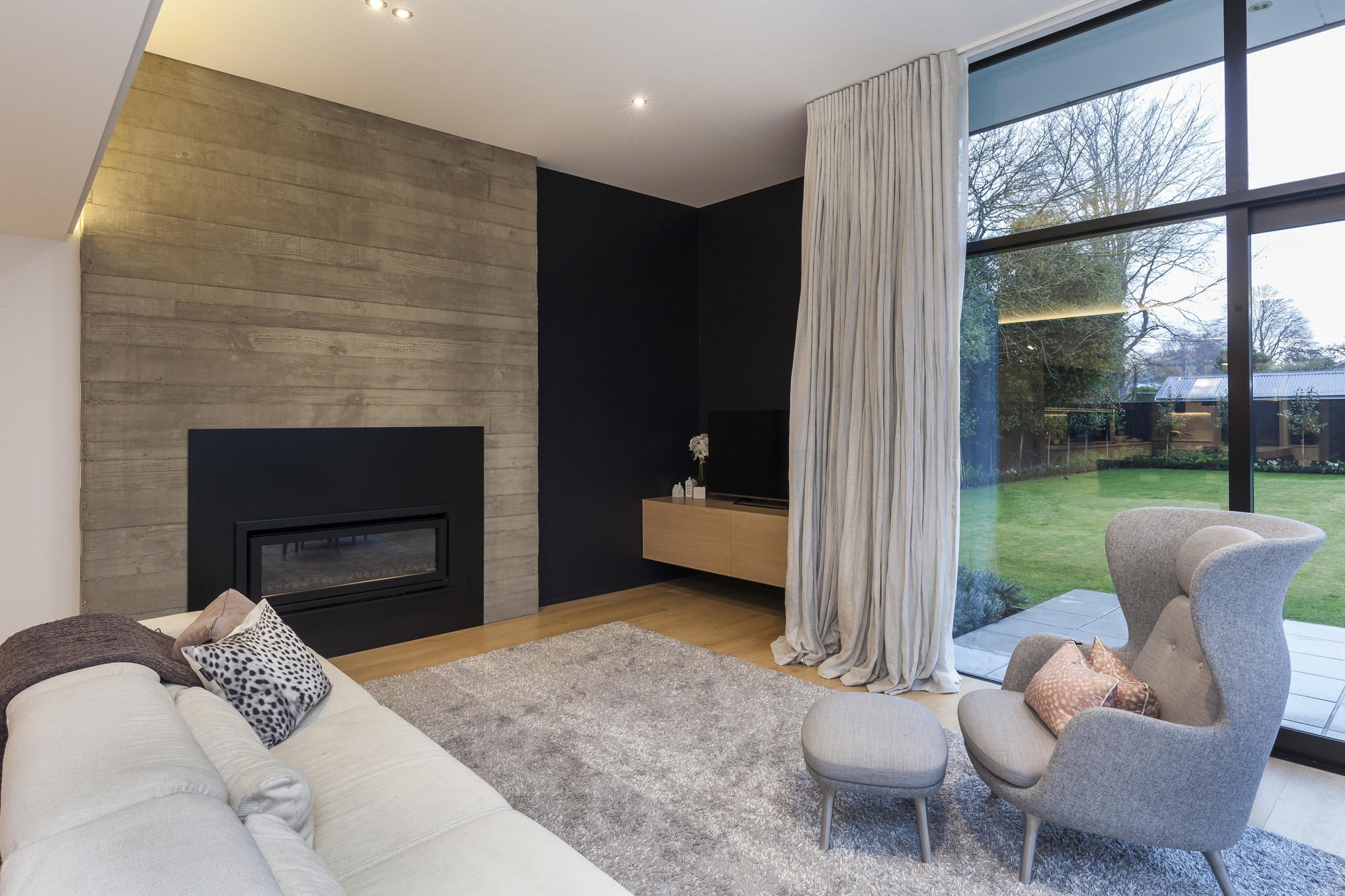 The lounge room featuring a textured concrete tilt panel with the fireplace