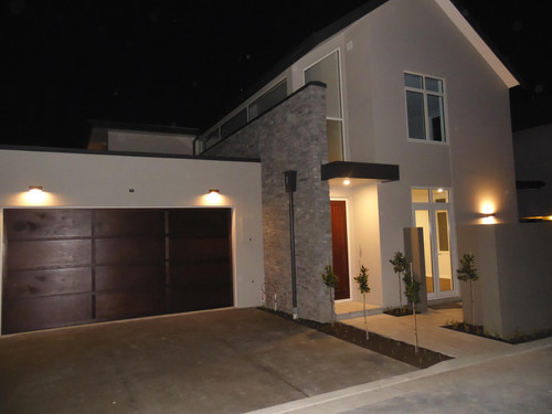 The front door and garage in cedar make a feature at night