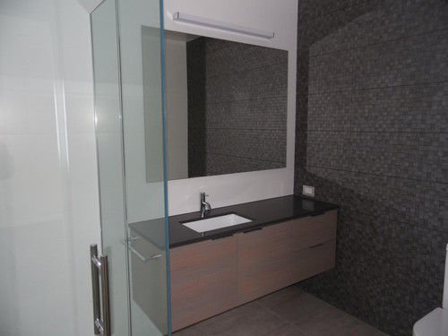 The bathroom vanity unit brings in that same woodwork with a feature tile