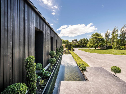 The exterior features grooved cedar weatherboard and large feature windows