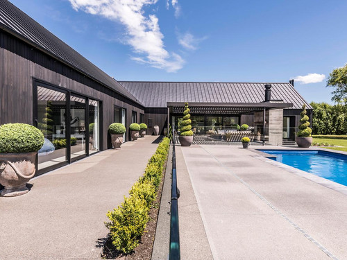 The pool area and exterior featuring grooved cedar weatherboard, large feature windows, tray roofing