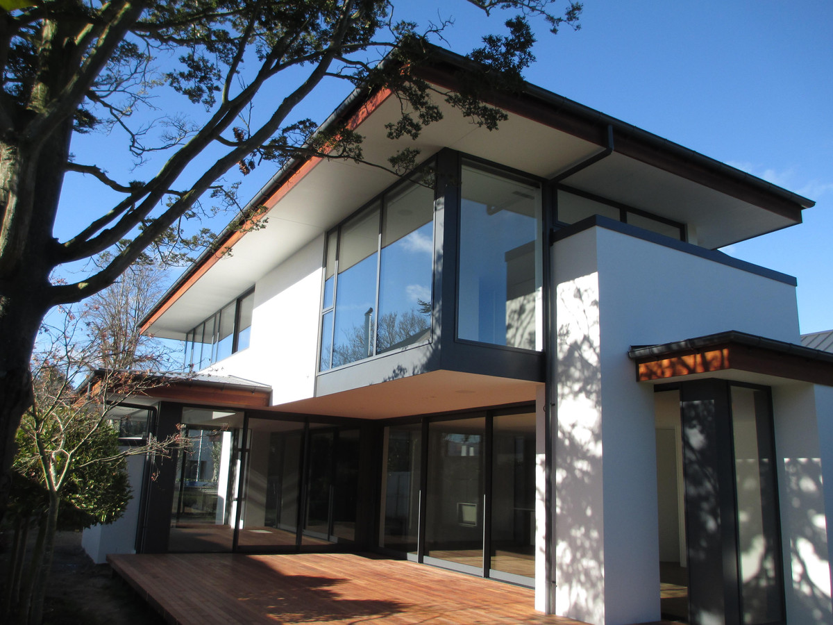 The home has large windows with overhanging soffits contrasting with hand-crafted cedar fascia