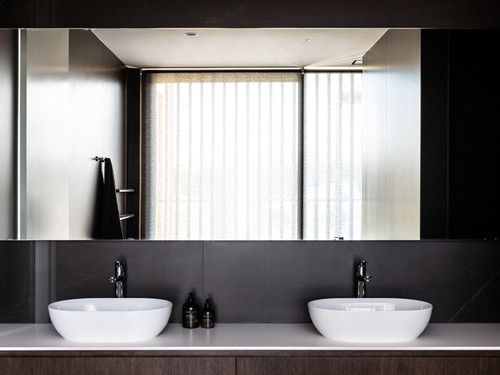 His and hers bathroom with dark wooden cabinetry
