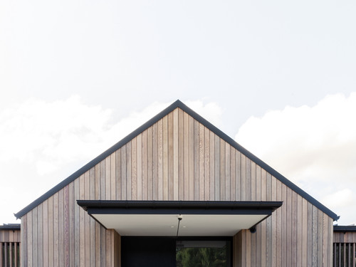 The natural timber finish of North Canterbury House matches in with the landscape