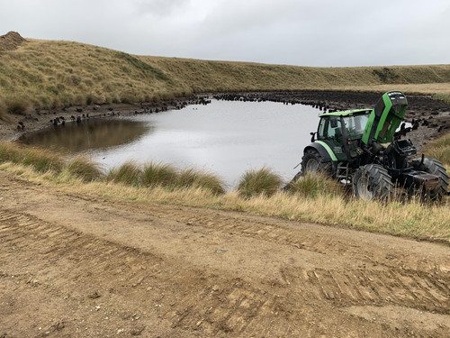 J G Smaill working with a dam to put in irrigation