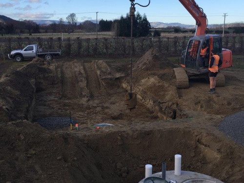 A septic tank being installed with an excavator