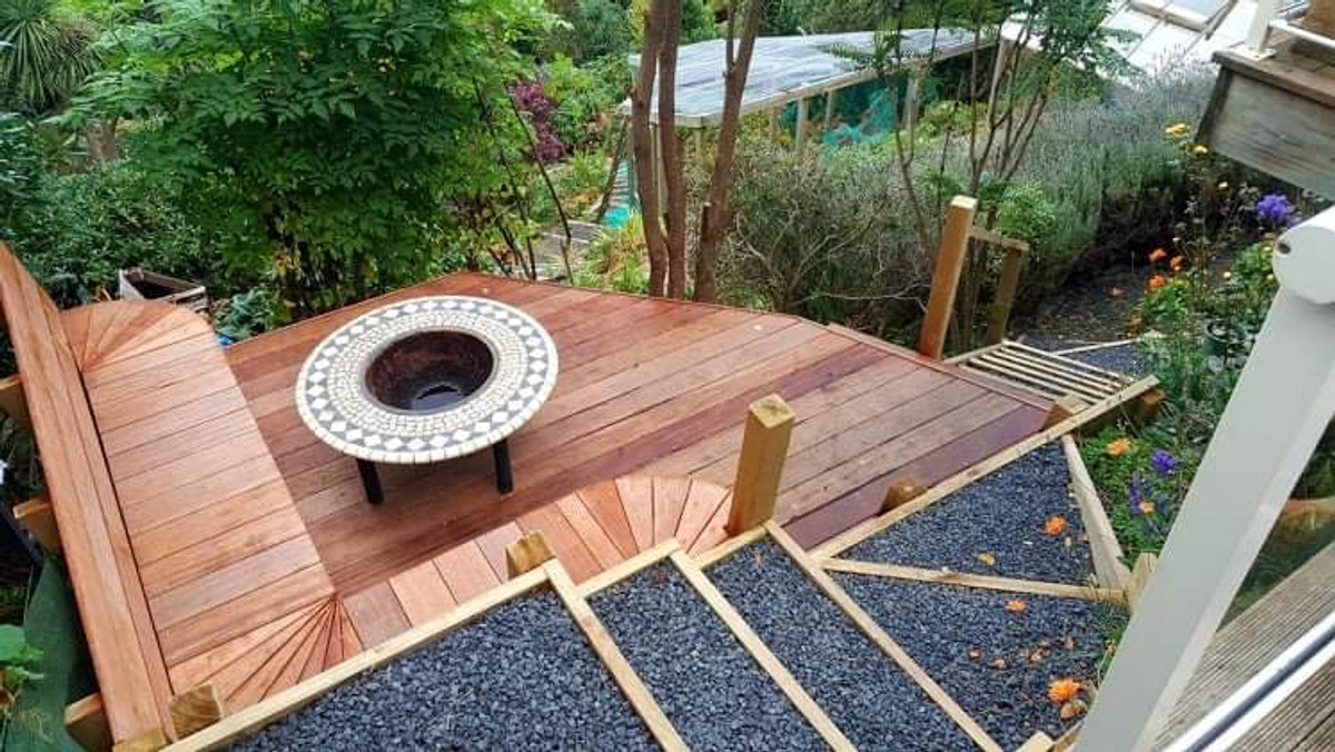 The fire pit area with decking and stairs by Outlet Homes