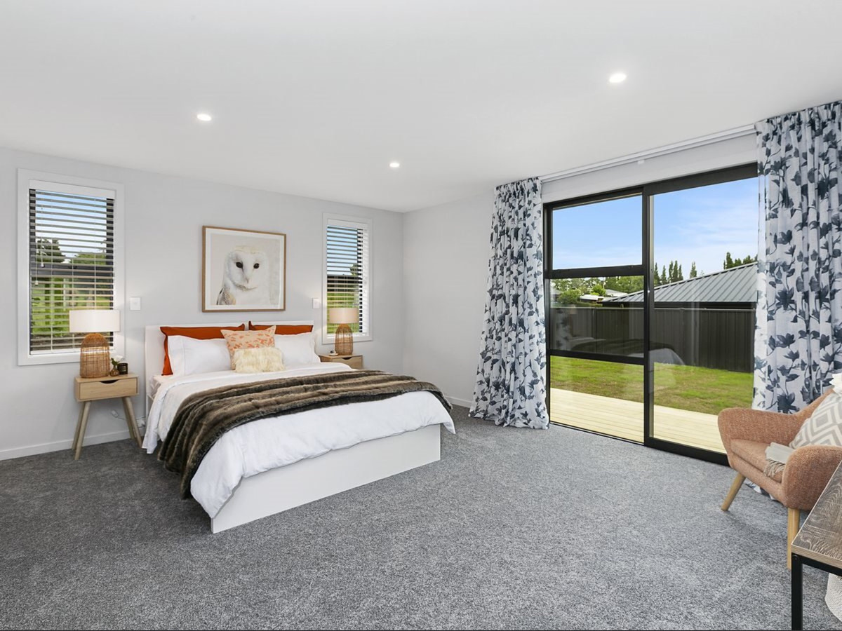 Bedroom with sliding doors leading to a deck