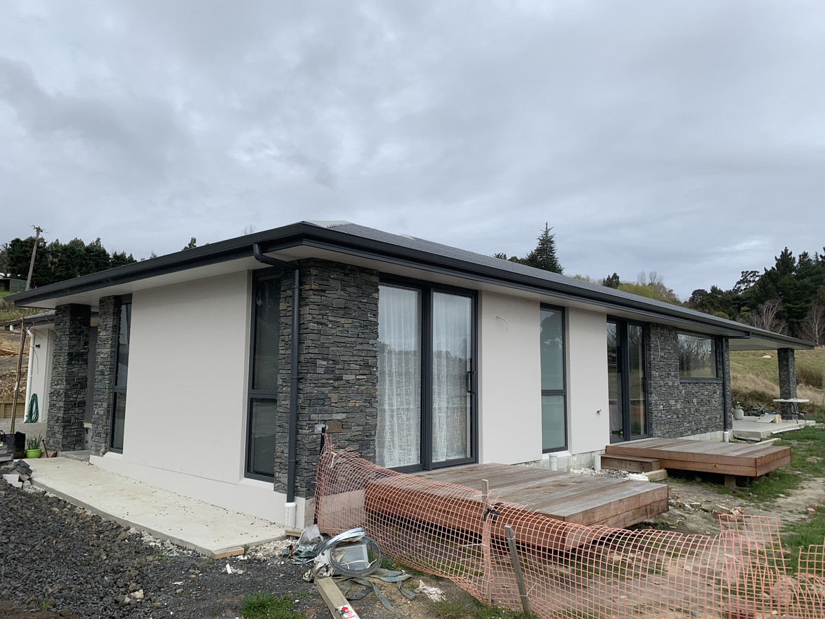 The finished new build utilizes brick, schist and plaster finish