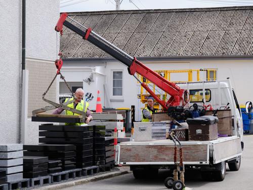 The crane lifting a granite base