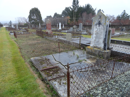 Read grave site with cracks and fallen fencing (before)