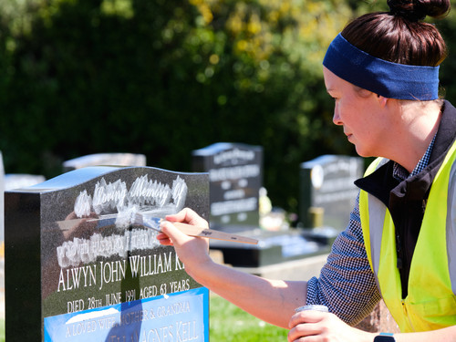 Jenna adding pigment to the lettering of this granite headstone