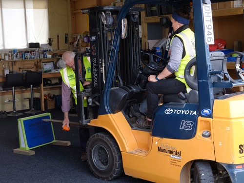 Operating a forklift to pick up a gravestone