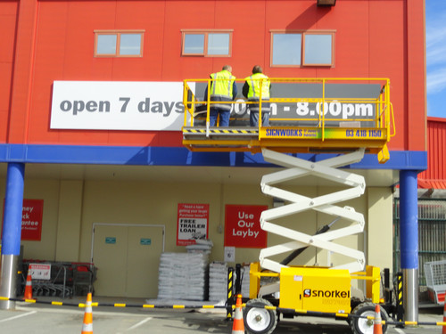 Working on The Warehouse sign is easy with the scissor lift